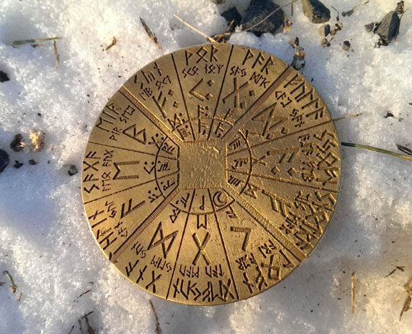 Rune engraved brass mirror on snow